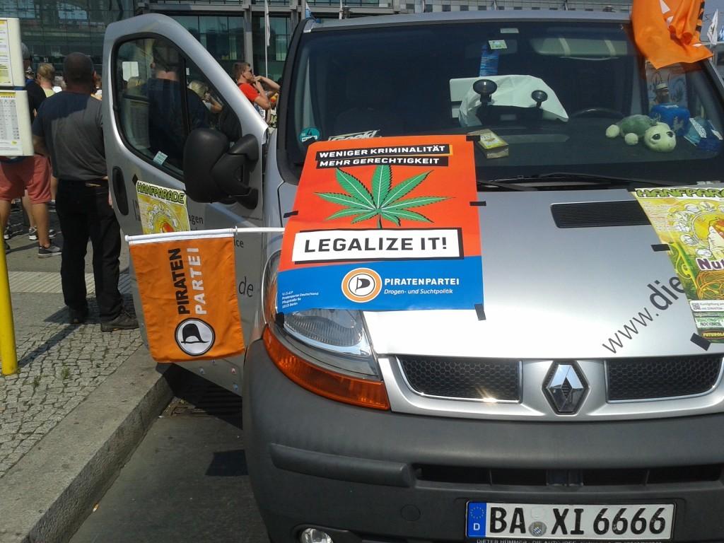 """Plakat """"Weniger Kriminalität - Mehr Gerechtigkeit - Legalize it"""" auf dem Auto der Piratenpartei"""